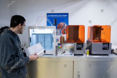 Senior 3D Specialist John Scott looks at a 3D printer making a two-part mold to create face masks with filter paper, at ABC Imaging in Washington, DC, USA, 01 April 2020. 3D printing is one of several printing and fabrication technologies that have seen an increase of demand due to the coronavirus COVID-19 pandemic. The same technology that was used to create signs and posters is now being used to create face masks and face guards. Two-part molds can be printed to create masks with filter paper, which is the same type of material used in heating, ventilation, and air conditioning filters.