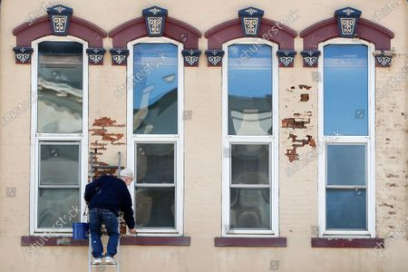 Steve Johnson, of Des Moines, Iowa, works on the front of a building on the town square, in Winterset, Iowa