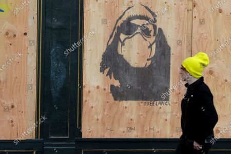Pedestrian walks past stencil art showing a self-portrait of Seattle music photographer Lance Mercer that was created by artist Chloe Guenther on the window of a boarded up business, in Seattle's Capitol Hill neighborhood. Most stores and businesses in the area are closed or only offering take-out food as a result of the outbreak of the new coronavirus, and state-wide stay-at-home orders from government officials