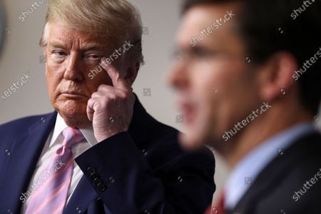 United States President Donald Trump touches his face as US Secretary of Defense Dr. Mark Esper speaks during the daily briefing on the novel coronavirus, COVID-19, in the Brady Press Briefing Room of the White House.
