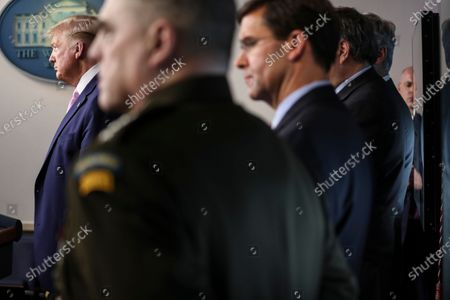United States President Donald Trump listens during the daily briefing on the novel coronavirus, COVID-19, in the Brady Press Briefing Room of the White House. Next to Trump, from left, United States Army General Mark A. Milley, Chairman of the Joint Chiefs of Staff; United States Secretary of Defense Dr. Mark Esper, US Attorney General William Barr, hidden, and National Security Advisor Robert O'Brien, hidden.