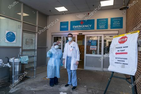 Stock Photo of Frontline hospital workers Gaetana Marra and Steven Tyler pose in front of emergency room at Maimonides Medical Center in Brooklyn where patients for COVID-19 have been treated