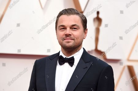 Leonardo DiCaprio arrives at the Oscars in Los Angeles. DiCaprio is helping to launch the $12 million America's Food Fund aimed at helping low-income families, the elderly and those whose jobs have been disrupted by the coronavirus pandemic. Among those teaming up for the launch are philanthropist Laurene Powell Jobs, Apple and the Ford Foundation