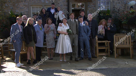 Ep 8778 Friday 17th April 2020 Vinny, as played by Bradley Johnson, takes his place in a family line picture outside the Woolpack, for Sam Dingle's, as played by James Hooton, and Lydia's, as played by Karen Blick, wedding, as Paul sitting in his car across the road watching...fully aware his son is still in Emmerdale after all..