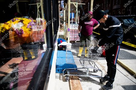 """Frank Schuch, right, and Tom Werner, who regularly work as masons before Pennsylvania Gov. Tom Wolf directed all """"non-life-sustaining"""" businesses to close, sanitizes shopping carts at the Rittenhouse Market in Philadelphia"""