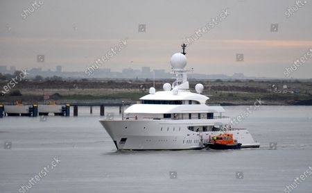 Stock Picture of Superyacht Ilona is pictured cruising the River Thames on her way to the London International Cruise Terminal and passing the cruise ship Magellan, laid up because of the Coronavitus pandemic. The 82m super yacht launched in 2003 is owned by Australian businessman Frank Lowe. The elegant yacht is equipped with a helicopter landing pad located above the bridge deck and the aft deck has a 10m swimming pool.