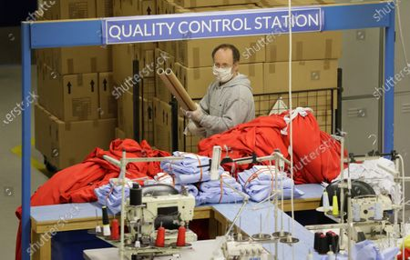Charge hand Robert Taylor prepares materials to sew into scrubs for the NHS at the factory of Fashion Enter in London, as the country is in lockdown to help curb the spread of the coronavirus, . The company normally makes fashion garments for Asos, but the shortages within the NHS mean that they have put their fashion orders on hold whilst they make PPE (personal protective equipment) to protect workers against the coronavirus outbreak