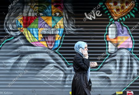 A woman wearing a protective face mask walks in front of a street graffiti depicting theoretical physicist Albert Einstein amid the ongoing coronavirus COVID-19 pandemic in Istanbul, Turkey, 03 April 2020. Turkey suspended all international flights and all inter-city travels are subject to local authorities' permission as part of measures to prevent the spread of the pandemic COVID-19 disease caused by the SARS-CoV-2 coronavirus. The country decided also to halt public events, temporarily shut down schools, and suspend sporting events.