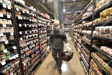 Alan Stotts wears a mask as he shops for groceries at Harmons grocery store, in Salt Lake City