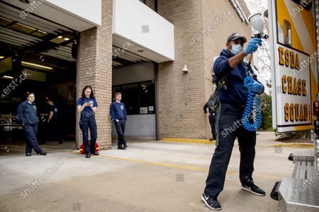 Volunteers watch as fellow EMT volunteer Ronald Felix, a full time police officer for Montgomery County, Md., sanitizes an ambulance at Bethesda-Chevy Chase Rescue Squad, in Bethesda, a suburb of Washington