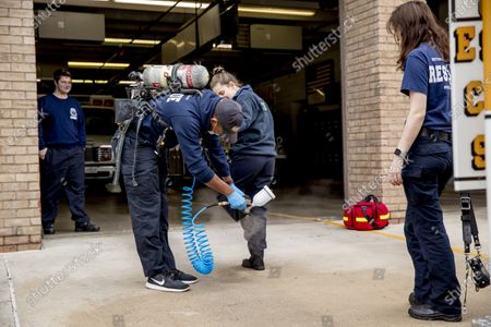 Volunteer EMT Ronald Felix, a full time police officer for Montgomery County, Md., second from left, sanitizes the shoes of his fellow volunteer EMT workers Alexandra Sachs, center, and Katherine Weber, right, after he finishes spraying an ambulance before they go out on calls at Bethesda-Chevy Chase Rescue Squad, in Bethesda, a suburb of Washington