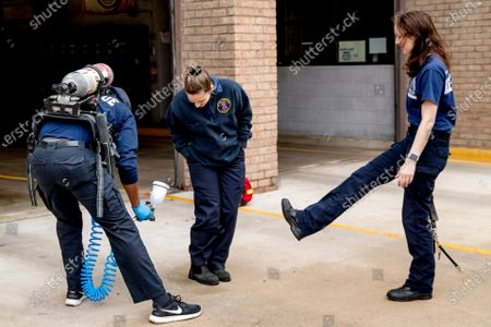 Stock Picture of Volunteer EMT Ronald Felix, a full time police officer for Montgomery County, Md., left, sanitizes the shoes of his fellow volunteer EMT workers Alexandra Sachs, center, and Katherine Weber, right, after he finishes spraying an ambulance before they go out on calls at Bethesda-Chevy Chase Rescue Squad, in Bethesda, a suburb of Washington