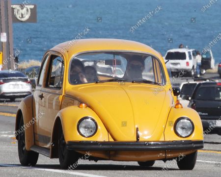 Stock Image of Ewan McGregor and children going for a ride in his old yellow bug in Malibu
