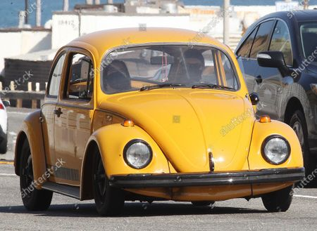 Stock Picture of Ewan McGregor and children going for a ride in his old yellow bug in Malibu