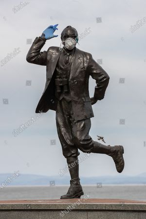 Stock Photo of A statue of popular British comedian Eric Morecambe is seen wearing protective gloves and a mask on the normally busy promenade of Morecambe Bay in North West England , as people heed instructions to stay at home on what is the warmest day of the year so far . NHS staff are complaining of shortages of vital PPE ( Personal Protective Equipment ) as they work to combat the Covid-19 outbreak in the UK . People are instructed to stay at home and avoid social contact as part of quarantine measures to prevent the spread of Coronavirus ( COVID-19 ) .
