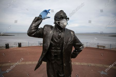 A statue of popular British comedian Eric Morecambe is seen wearing protective gloves and a mask on the normally busy promenade of Morecambe Bay in North West England , as people heed instructions to stay at home on what is the warmest day of the year so far . NHS staff are complaining of shortages of vital PPE ( Personal Protective Equipment ) as they work to combat the Covid-19 outbreak in the UK . People are instructed to stay at home and avoid social contact as part of quarantine measures to prevent the spread of Coronavirus ( COVID-19 ) .