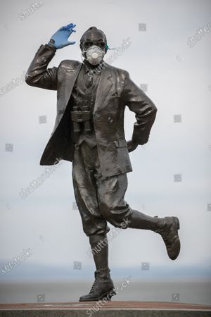 Stock Picture of A statue of popular British comedian Eric Morecambe is seen wearing protective gloves and a mask on the normally busy promenade of Morecambe Bay in North West England , as people heed instructions to stay at home on what is the warmest day of the year so far . NHS staff are complaining of shortages of vital PPE ( Personal Protective Equipment ) as they work to combat the Covid-19 outbreak in the UK . People are instructed to stay at home and avoid social contact as part of quarantine measures to prevent the spread of Coronavirus ( COVID-19 ) .