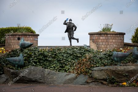 Stock Image of A statue of popular British comedian Eric Morecambe is seen wearing protective gloves and a mask on the normally busy promenade of Morecambe Bay in North West England , as people heed instructions to stay at home on what is the warmest day of the year so far . NHS staff are complaining of shortages of vital PPE ( Personal Protective Equipment ) as they work to combat the Covid-19 outbreak in the UK . People are instructed to stay at home and avoid social contact as part of quarantine measures to prevent the spread of Coronavirus ( COVID-19 ) .