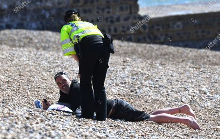 A police officer asks people to leave the beach in Brighton on a sunny Sunday during the Covid-19 outbreak. The Government has urged people to stay indoors, and warned that exercise outside the home could be banned if people ignore social distancing rules.