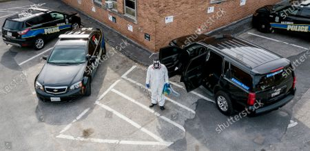 Stock Photo of An aerial picture shot with a drone shows owner Reggie Haskins and Lead Tech Emmanuel Walker of Bio Aftermath Solutions clean all of the patrol vehicles for the Southwestern District of the Baltimore Police Department, Batlimore, Maryland, USA, 05 April 2020. After at least one officer tested positive for coronavirus, Police Commissioner Michael Harrison ordered the entire district closed for cleaning and ordered the quarantine of the entire district's personnel. Each remaining district sent one sergeant and eight officers to staff the district's policing responsibilities.