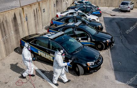 Stock Picture of An aerial picture shot with a drone shows owner Reggie Haskins and Lead Tech Emmanuel Walker of Bio Aftermath Solutions clean all of the patrol vehicles for the Southwestern District of the Baltimore Police Department, Batlimore, Maryland, USA, 05 April 2020. After at least one officer tested positive for coronavirus, Police Commissioner Michael Harrison ordered the entire district closed for cleaning and ordered the quarantine of the entire district's personnel. Each remaining district sent one sergeant and eight officers to staff the district's policing responsibilities.