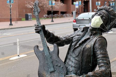 """The Daryl Smith sculpture """"The Electric Lady Studio Guitar,"""" a statue of the late rock guitarist Jimi Hendrix located on Seattle's Broadway Avenue, is pictured wearing a face mask. The original source of the COVID-19 outbreak in the United States, the Seattle-area has seen a drop in new cases. On Saturday, United States President Donald Trump announced the removal of 300 federal medical beds from the city for reallocation to other areas."""