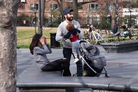 NEW YORK, UNITED STATES - APRIL 05, 2020: A young couple with a kid enjoy the afternoon sun in Washington Square Park amid the coronavirus pandemic in New York City. The state of New York has over 122,000 confirmed corona virus cases and over 4,000 deaths.