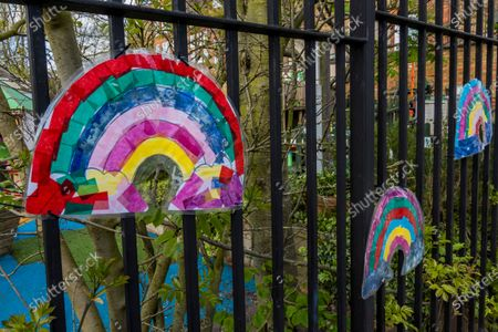 Stock Picture of Rainbow drawings on railings of the Honeywell Nursery in Battersea - A 'symbol of hope' inspired by a drawing (pictured) by Sir Peter Blake, the artist who designed the cover of The Beatles' Sgt. Pepper album. The Evening Standard asked Sir Peter to create his version while he is in self-isolation. The 'lockdown' continues for the Coronavirus (Covid 19) outbreak in London.