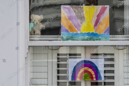 Rainbow drawings in windows with a Teddy Bear - A 'symbol of hope' inspired by a drawing (pictured) by Sir Peter Blake, the artist who designed the cover of The Beatles' Sgt. Pepper album. The Evening Standard asked Sir Peter to create his version while he is in self-isolation. The 'lockdown' continues for the Coronavirus (Covid 19) outbreak in London.