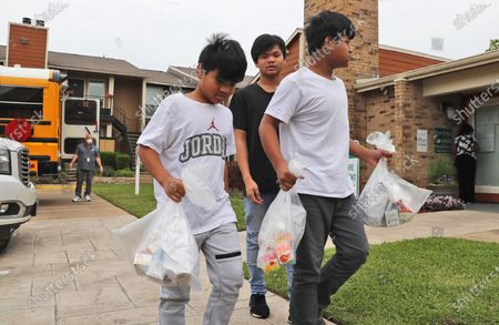 Brothers from left, Aiden Lay, 10, Andrew Lay, 12, and Alex Lay, 11, carry their school meals after picking them up from an apartment complex distribution site in Dallas, . With schools closured amid CODVID-19 coronavirus concerns, Richardson Independent School district is providing meals for all students at specified schools and apartment communities