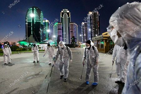 Municipal worker wearing protective suit sprays disinfectant in an area at the center of Grozny, Russia, . Ramzan Kadyrov, strongman leader of Russia's province of Chechnya, has taken extreme measures to fight the spread of the new coronavirus in the region, vowing Monday not to let anyone who is not a formal resident of Chechnya into the area.The new coronavirus causes mild or moderate symptoms for most people, but for some, especially older adults and people with existing health problems, it can cause more severe illness or death