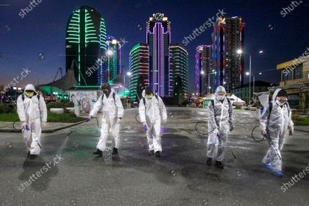 Municipal workers wearing protective suits spray disinfectant in an area in the center of Grozny, Russia, . Ramzan Kadyrov, strongman leader of Russia's province of Chechnya, has taken extreme measures to fight the spread of the new coronavirus in the region, vowing Monday not to let anyone who is not a formal resident of Chechnya into the area.The new coronavirus causes mild or moderate symptoms for most people, but for some, especially older adults and people with existing health problems, it can cause more severe illness or death
