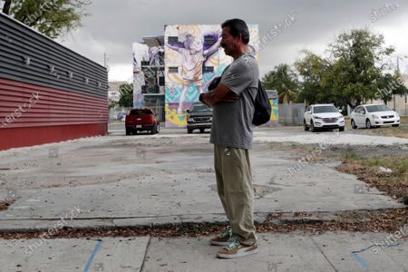 Man waits outside of Marcus Samuelsson's Red Rooster Restaurant where a meal will be distributed to those in need during the new coronavirus pandemic, in the Overtown neighborhood of Miami. Samuelsson has partnered with chef Jose Andres' World Central Kitchen to provide meals to those affected by the new coronavirus outbreak