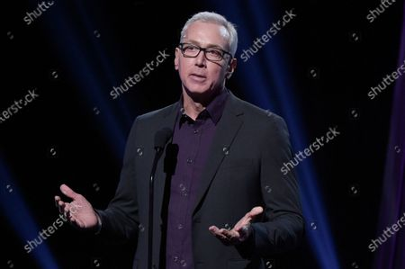 """Drew Pinsky speaking at the 2019 iHeartRadio Podcast Awards in Burbank, Calif. Pinsky has apologized for a series of statements unspooled in a recent video where he downplayed the coronavirus and suggested that it was a """"press-induced panic"""