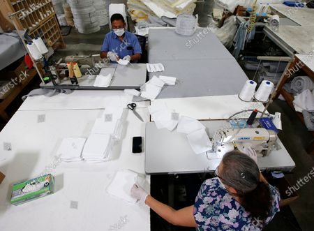 Maria Rodriguez, right, and Jose Gonzalez, left, work on making non-N95 face masks as the Ortho Mattress company is repurposing their factory to make the masks due to the coronavirus pandemic, in Phoenix. Ortho Mattress has a daily goal of making 1,000 of the masks supporting the demand in the community
