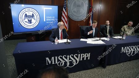Mississippi Gov. Tate Reeves, second from left, discusses how the state is responding to COVID-19 as the numbers of deaths and of those people who have tested positive with the disease continues to rise, during his news conference in Jackson, Miss., . Reeves is flanked to the left by Jim Craig, Senior Deputy and Director of Health Protection at Mississippi State Department of Health, Greg Michel, Executive Director of the Mississippi Emergency Management Agency, second from right and Adjutant General of the Mississippi National Guard Major General Janson D. Boyles, right, and all provided agency updates as well