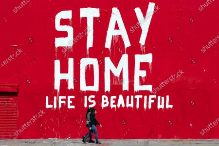 Two women wearing face masks walk past a mural reading 'Stay Home Life Is Beautiful' amid the coronavirus pandemic in Los Angeles, California, USA, 07 April 2020. Countries around the world are taking increased measures to stem the spread of the SARS-CoV-2 coronavirus which causes the Covid-19 disease.