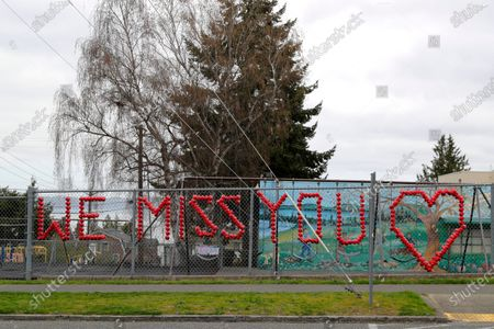 """Stock Image of Sign made with plastic cups that reads """"We Miss You"""" is shown on the fence of Lowell Elementary School in Tacoma, Wash., . On Monday, Washington Gov. Jay Inslee announced that schools will remain physically closed for the remainder of the school year due to the coronavirus outbreak, and that public and private school students will continue distance learning through June"""