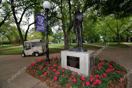 Stock Image of A campus police officer drives past the statue of John Wesley, founder of the Methodist Church, at Millsaps College in Jackson, Miss. The students are gone in face of the coronavirus. The private liberal arts college, affiliated with the United Methodist Church, faces a different set of financial and enrollment challenges because of the virus. At present, the school has switched to online teaching