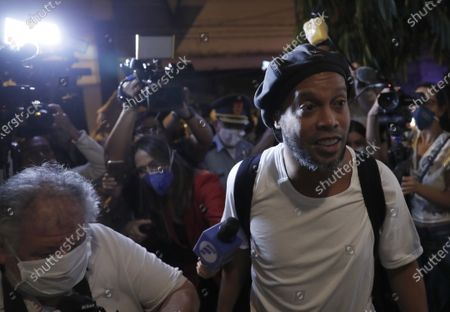 Surrounded by the media, former Brazilian soccer star Ronaldinho arrives at a hotel where he is to stay under house arrest in Asuncion, Paraguay, . Ronaldinho and his brother Roberto De Assis Moreira spent a month in jail accused of entering Paraguay with fake passports