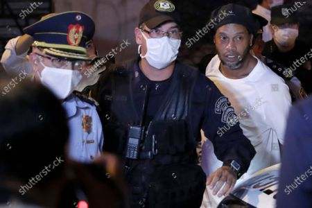 Former Brazilian soccer star Ronaldinho, right, arrives at a hotel where he is to stay under house arrest in Asuncion, Paraguay, . Ronaldinho and his brother Roberto De Assis Moreira spent a month in jail accused of entering Paraguay with fake passports