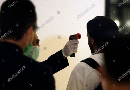 Former Brazilian soccer star Ronaldinho has his temperature taken to check for the symptoms of the new coronavirus, as arrives at a hotel where he is to stay under house arrest in Asuncion, Paraguay, . Ronaldinho and his brother Roberto De Assis Moreira spent a month in jail accused of entering Paraguay with fake passports