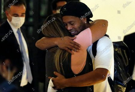 Former Brazilian soccer star Ronaldinho is embraced by a woman as he arrives at a hotel where he is to stay under house arrest in Asuncion, Paraguay, . Ronaldinho and his brother Roberto De Assis Moreira spent a month in jail accused of entering Paraguay with fake passports