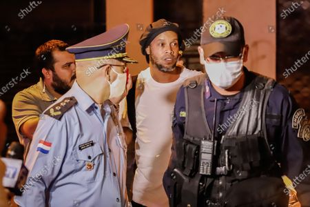 Brazilian former soccer player Ronaldinho Gaucho (C) arrives at the Hotel Palmaroga in Asuncion, Paraguay, 07 April 2020. Ronaldinho and his brother entered the hotel to serve house arrest after leaving the police headquarters. The brothers remained in police custody for a month after being charged with entering Paraguay with fake passports and were released on a 1.6-million US dollar bail.