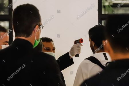 Brazilian former soccer player Ronaldinho Gaucho (2-R) has his temperature checked as he arrives at the Hotel Palmaroga in Asuncion, Paraguay, 07 April 2020. Ronaldinho and his brother entered the hotel to serve house arrest after leaving the police headquarters. The brothers remained in police custody for a month after being charged with entering Paraguay with fake passports and were released on a 1.6-million US dollar bail.