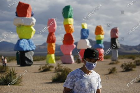Man wears a mask on his face while visiting the artwork titled Seven Magic Mountains by artist Ugo Rondinone amidst the coronavirus outbreak, near Jean, Nev., south of Las Vegas