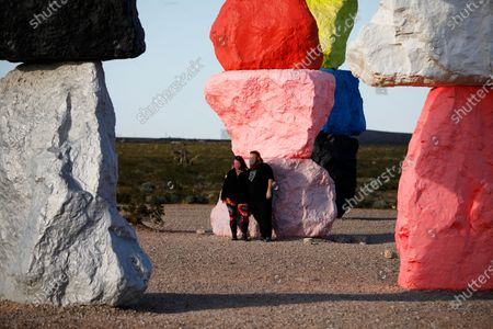People wear masks while visiting the artwork titled Seven Magic Mountains by artist Ugo Rondinone amidst the coronavirus outbreak, near Jean, Nev., south of Las Vegas