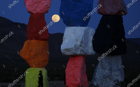 Supermoon rises behind the artwork titled Seven Magic Mountains by artist Ugo Rondinone, in Las Vegas