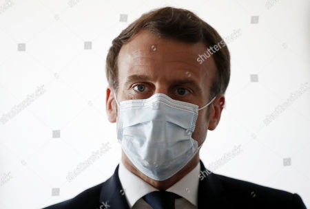 French President Emmanuel Macron, wearing a protective face mask, talks with health workers as he visits a medical center in Pantin near Paris as the spread of the coronavirus disease (COVID-19) continues in France