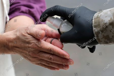 Woman is given hand sanitizer as she waits outside of Marcus Samuelsson's Red Rooster Restaurant for a free meal during the new coronavirus pandemic, in the Overtown neighborhood of Miami. Samuelsson has partnered with chef Jose Andres' World Central Kitchen to distribute meals to those in need